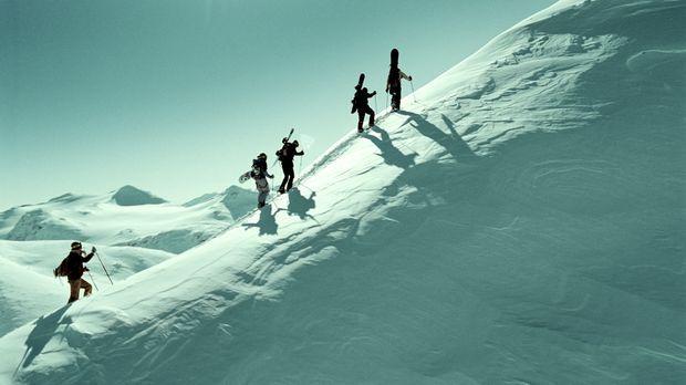Eine Gruppe von Snowboardern ist auf dem Weg durch die einsame Bergwelt Norwe...