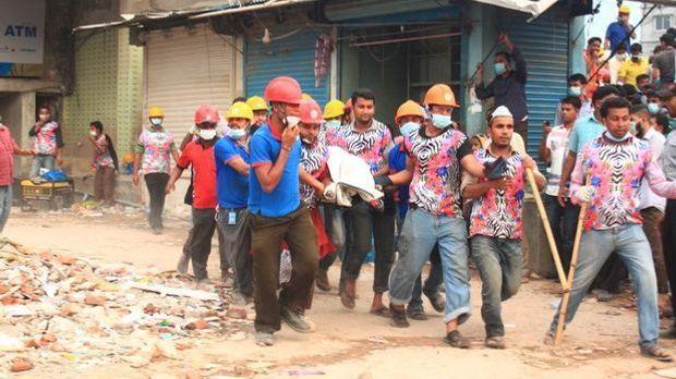 Arbeiter tragen einen Überlebenden aus den Trümmern des Rana-Plaza-Gebäude.