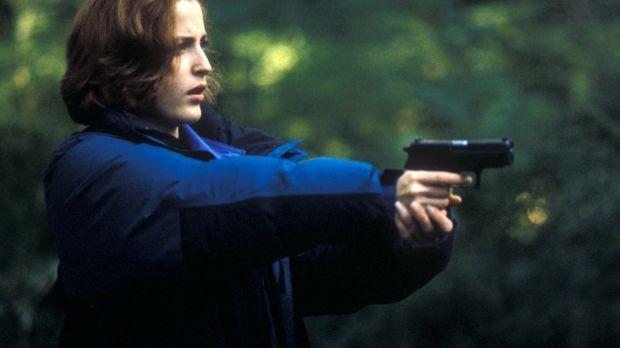 Scully (Gillian Anderson) zielt auf einen unsichtbaren Gegner, den sie zunäch...