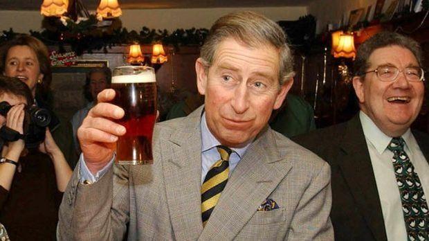 Prince Charles in einem Pub mit einem Glas Bier in der Hand