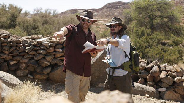 Josh Gates (l.) und der Forscher Adam Cruise (r.) suchen in der Kalahari Wüst...